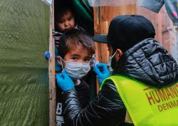 A refugee chid is given a face mask in the Moria refugee camp in Greece.