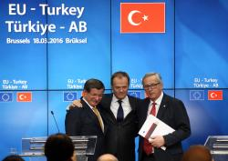Turkey's Prime Minister, Ahmet Davutoglu (L) shakes hands with President of the European Council, Donald Tusk and President of the European Commission, Jean-Claude Juncker, after a press conference to discuss the migrant deal reached between Turkey and EU states, during a two-day EU summit, on March 18, 2016 in Brussels, Belgium.