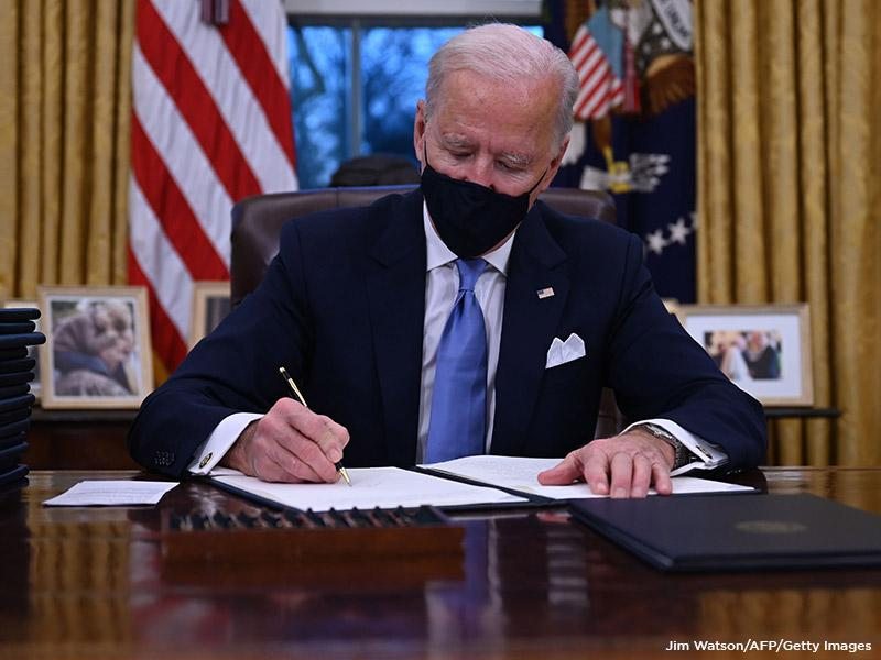 US President Joe Biden signs orders at the White House in Washington, DC, January 20, 2021. (Jim Watson/ AFP/Getty Images)