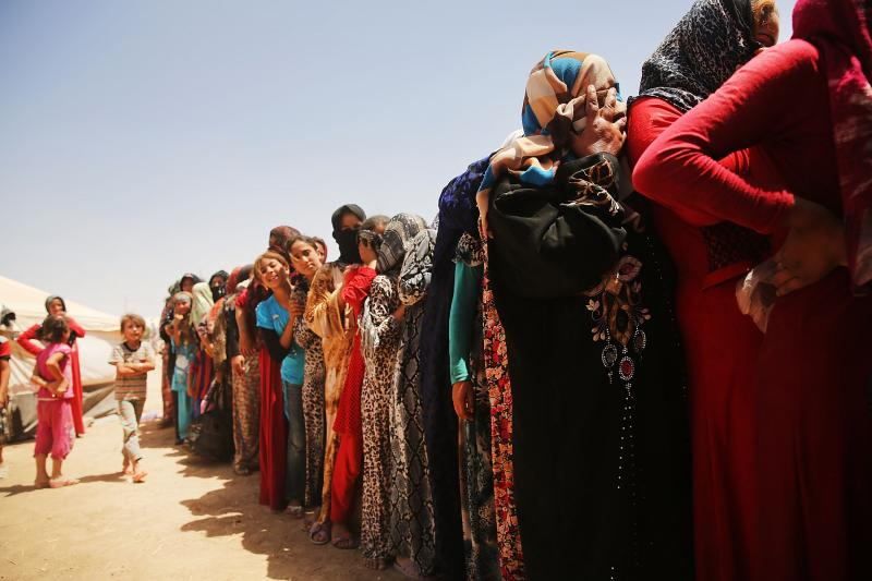 Iraqi women at the Khazair displacement camp wait for food and other items being dispensed by the Iraqi Red Crescent society on June 30, 2014 in Khazair, Iraq.