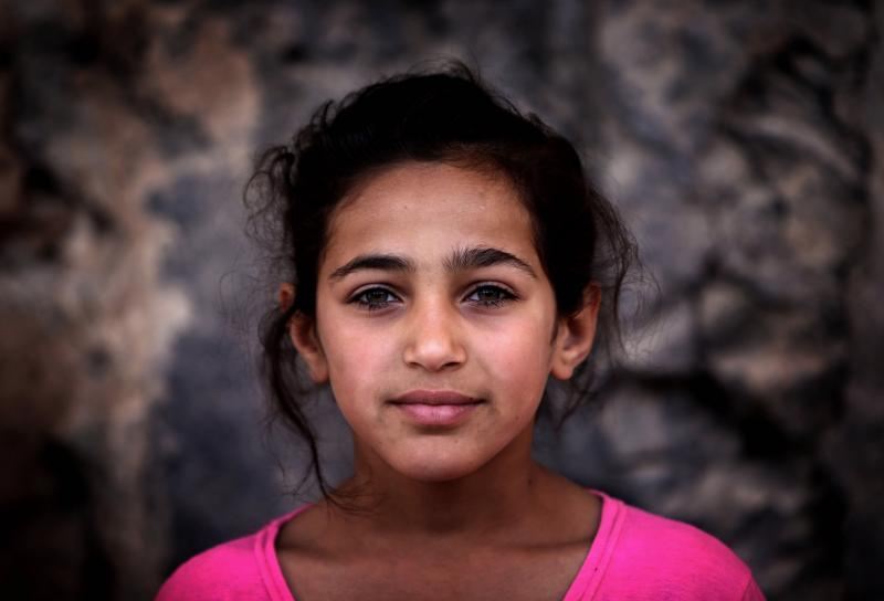 A Young Syrian-Kurdish refugee poses for a picture in a makeshift refugee camp in Iraq's Mosul region. Remembering Female Refugees on International Women's Day.